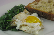 Photo of Runny Eggs on Wilted Greens